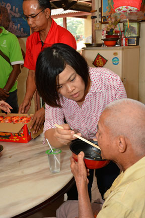 An occasion for goodwill: Tee Mei Fong, Senior Marketing Communications Executive helping a resident with the tasty Chinese New Year delicacy, Yee Sang.