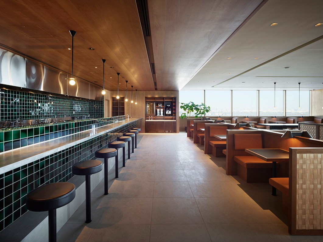 The Noodle Bar is framed with details such as glazed screens, green ceramic tiles, cherry wood walls and a limestone floor