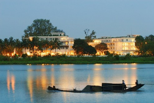 A sampan sweeps by La Residence Hotel & Spa on the Perfume River