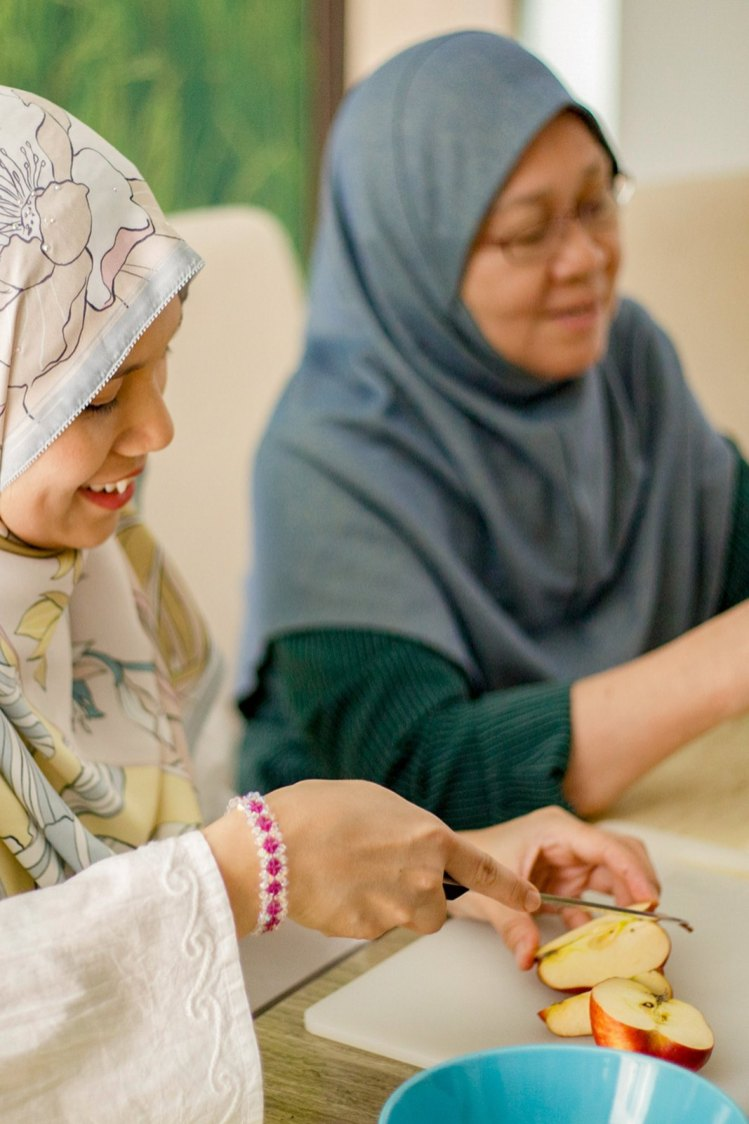 Two Malay woman prepares food for dinner at home