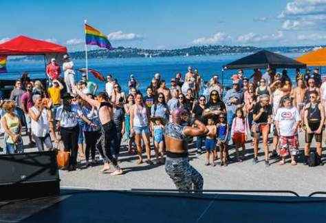 Photo of people standing with pride flags watching a performer