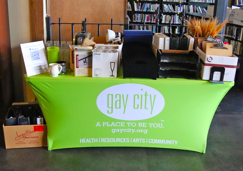 Photo of various items on a table with a green Gay City tablecloth