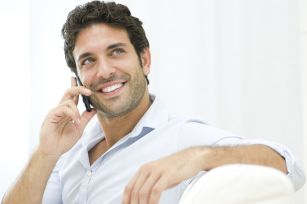 Young and healthy man smiling and talking on smart phone at home