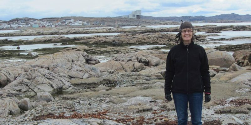 Dr. Ursula Kelly stands on Fogo Island with inn in the background