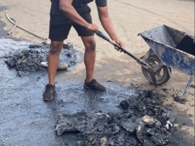 John Dumelo helps clean chucked gutters in his constituency