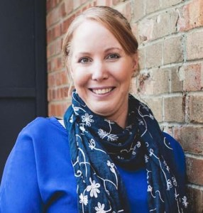 Michelle Large works at GB Solutions, a recruitment agency in Gloucestershire. Michelle leans on a brick wall smiling wearing a blue top and navy scarf