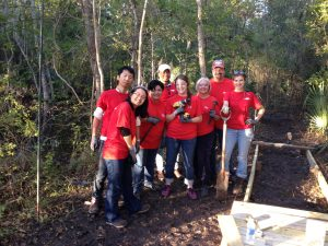 group of smiling volunteers in red shirts