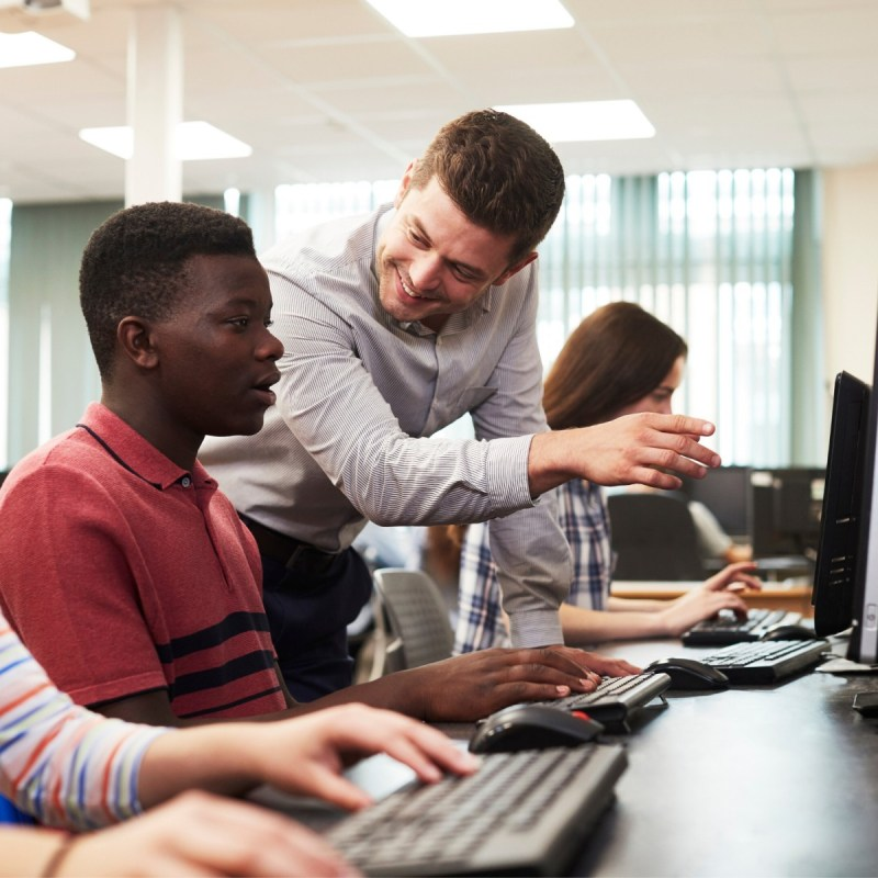 Academies - Teacher helping students at computers