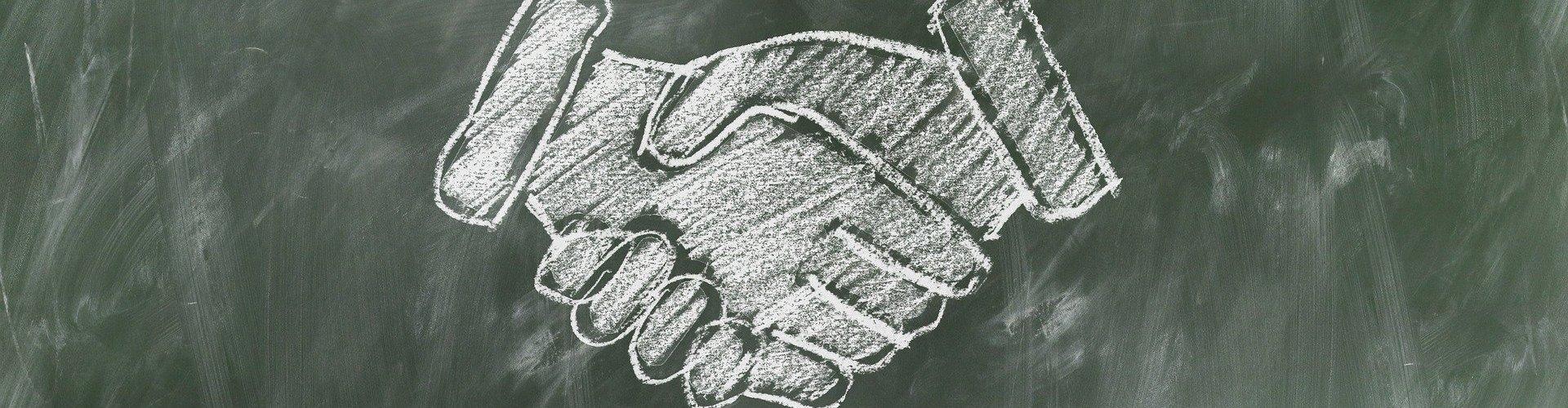 Shaking hands drawn on blackboard in chalk