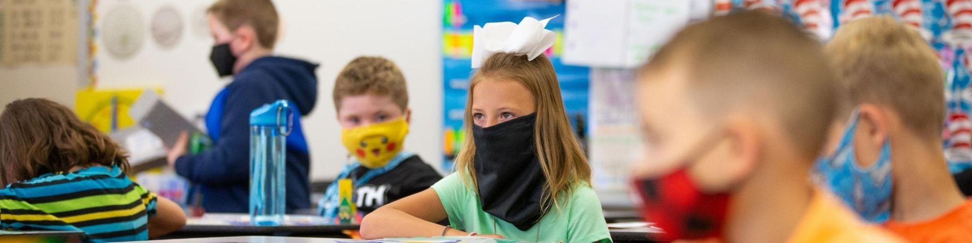 Students sitting at desks, wearing face masks.
