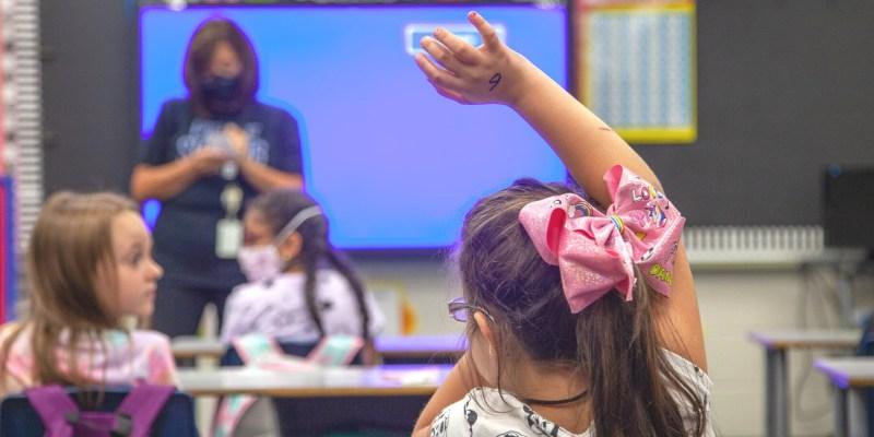 Student raising her hand in class