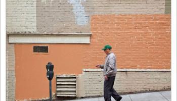 Man Walking Past Painted Brick Wall