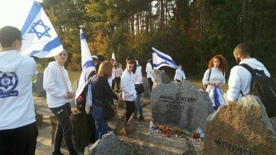 Młodzi Izraelczycy przy kamieniu upamiętniającym Janusza Korczaka i dzieci z sierocińca