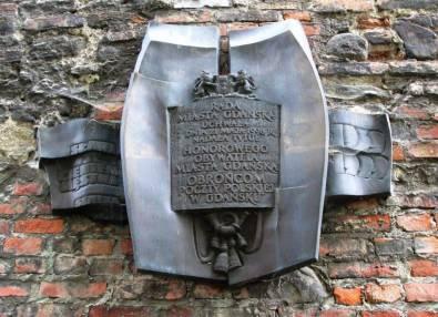 Tablica na murze upamiętniająca nadanie Obrońcom Poczty Polskiej tytułów Honorowych Obywateli Miasta Gdańska