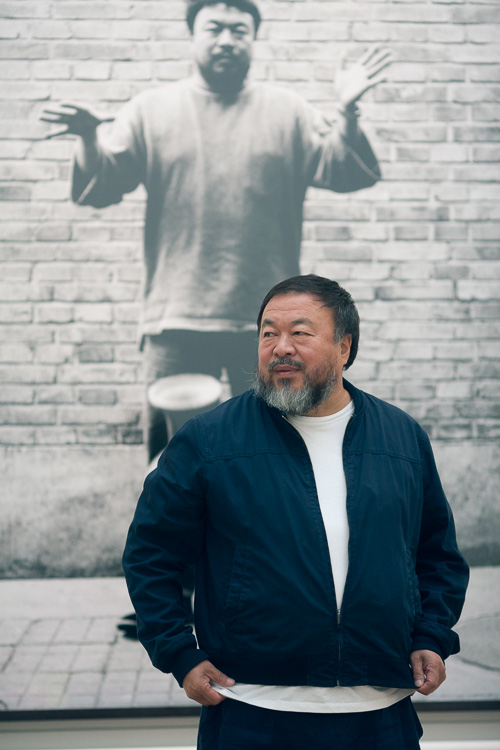 Ai Weiwei with one of his photographs from Dropping a Han Dynasty Urn, Royal Academy of Arts, 2015. Photo courtesy of Royal Academy of Arts, London