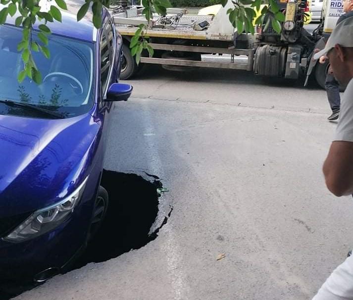 """O mașină a fost """"înghițită"""" de asfalt pe bulevardul Dacia din municipiul Craiova. Asfaltul din parcare a cedat sub greutatea autovehiculului"""