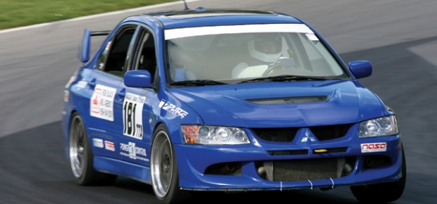 blue Mitsubishi Lancer Evo cornering at speed