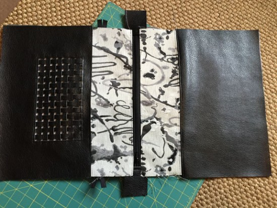 Zipper is sewn in to the front and back of the bag and the lining.