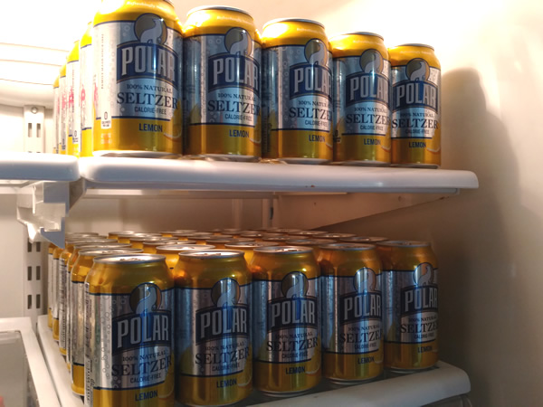 Two refrigerator shelves fill with Polar lemon seltzer in 12 ounce cans.