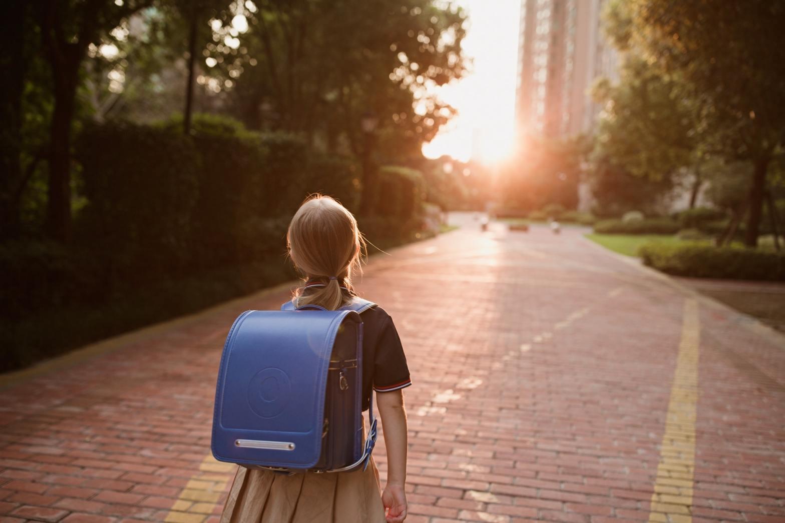 Schoolgirl back to school. Pupil in uniform and backpack outdoor