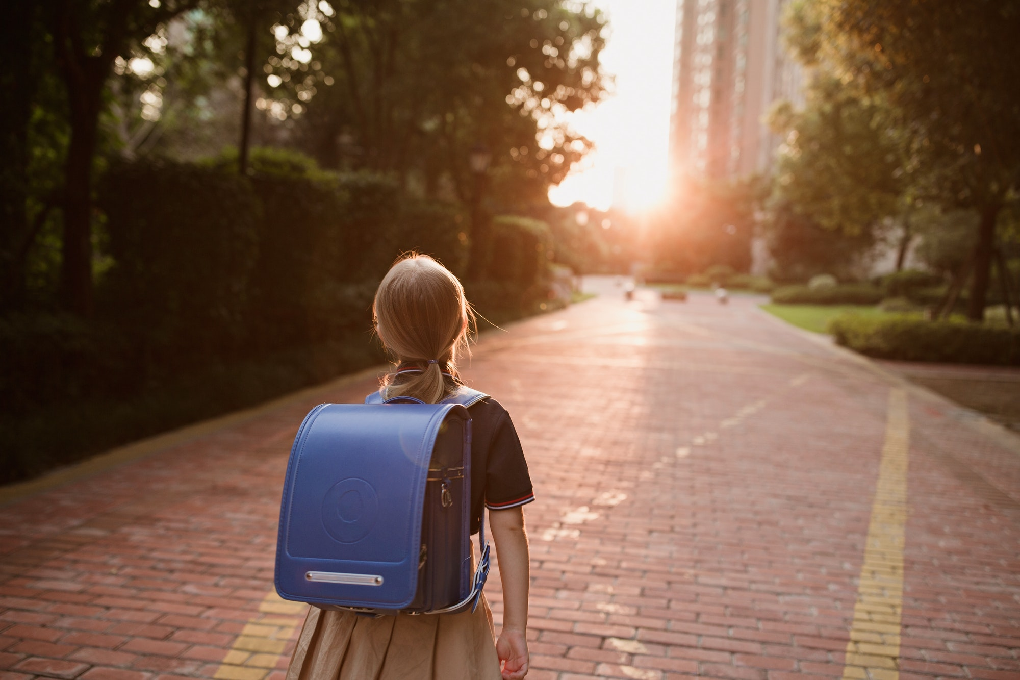 Schoolgirl back to school. Pupil in uniform and backpack outdoor