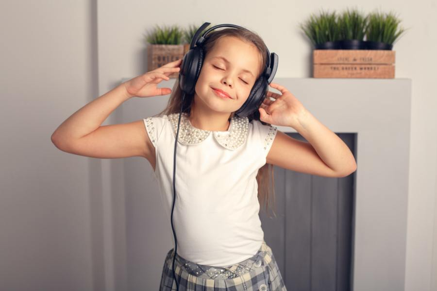 beautiful schoolgirl listens to a song in the headphones. The co