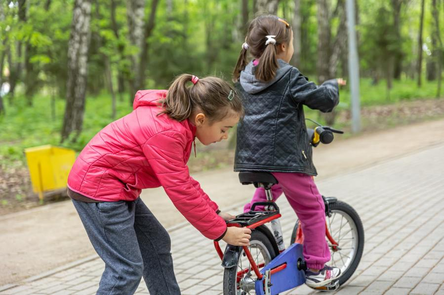 Children ride a bike for a walk in the park.