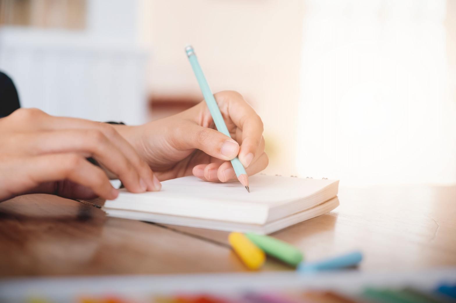 Female hand writing notebook.