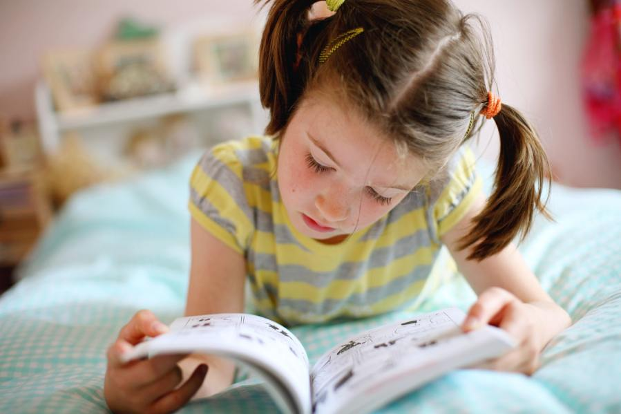 Young girl with pigtails laying on her bed reading a comic book