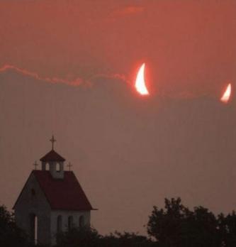 Moon partially hidden behind clouds looks like devil horns