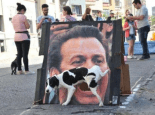 Dog peeing on poster of man's face