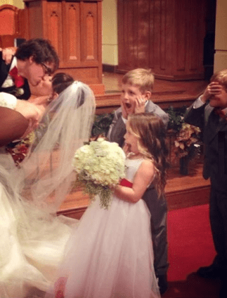 Three children looked shocked as bride and groom kiss