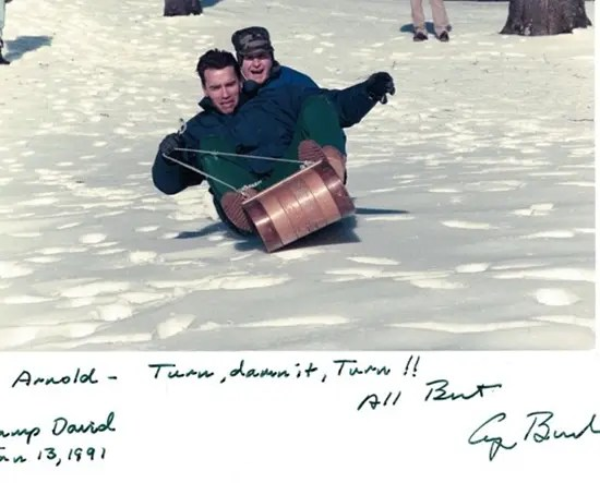 Arnold Schwarzenegger sledding with President George H. Bush at Camp David.