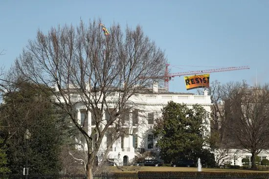 Resist flag hanging from crane by White House