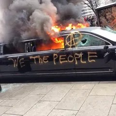 We the people scrawled on burning car