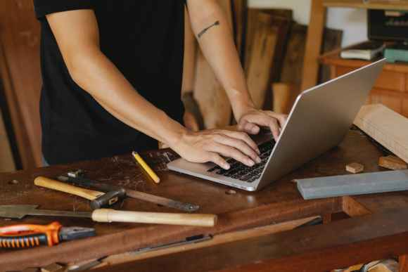 man checking information on laptop on timber table