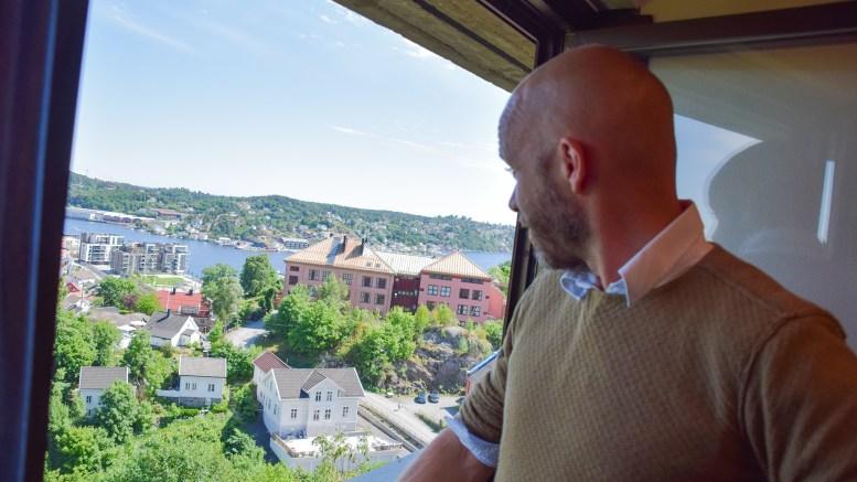 BUSSFORBINDELSE: Fra møterommet Vegår i Fylkeshuset ser Kristoffer Lyngvi-Østerhus ferjeleiet på Skilsø, som i årevis ikke har hatt bussforbindelse. Nå øyner han en ny mulighet for å få det på plass. Foto: Esben Holm Eskelund