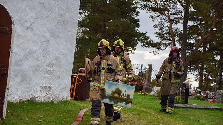 REDDET VERDIER: Etter å ha fått kontroll på brannen, ble uerstattelige kulturhistoriske verdier reddet ut av en brannskadet Tromøy kirke. Til alt hell var det bare en øvelse. Foto: Esben Holm Eskelund