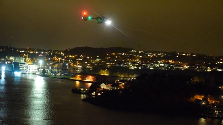 STOR LETEAKSJON: Her søker luftambulansen med lyskaster i Tromøysund etter en savnet person lørdag kveld. Foto: Esben Holm Eskelund