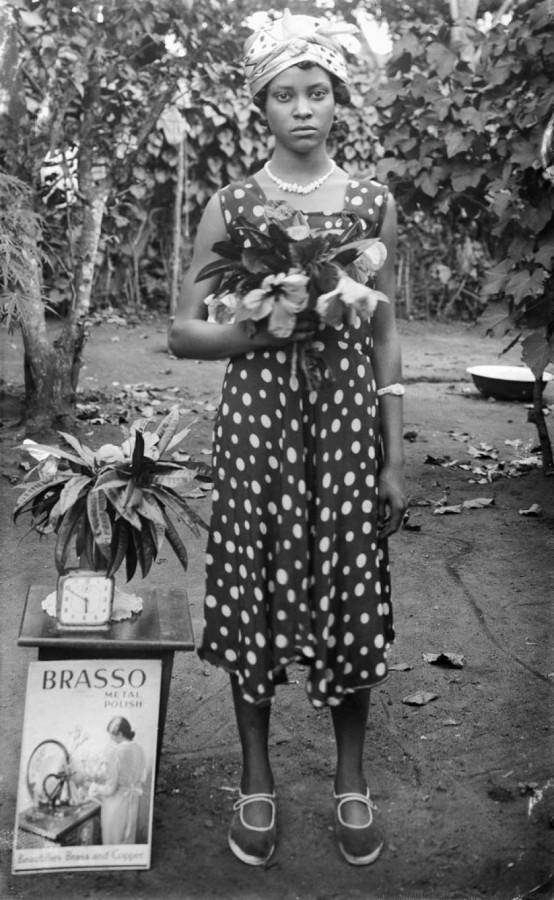 "Mulher de pé com flores; relógio na mesa; ""Brasso metal polish"" [Dame Merry Oritsetimeyin Ehanire nee Cardigan (mãe de Osagie Ehanire)]"