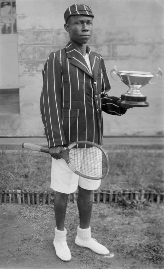 Menino com raquete de tênis e troféu