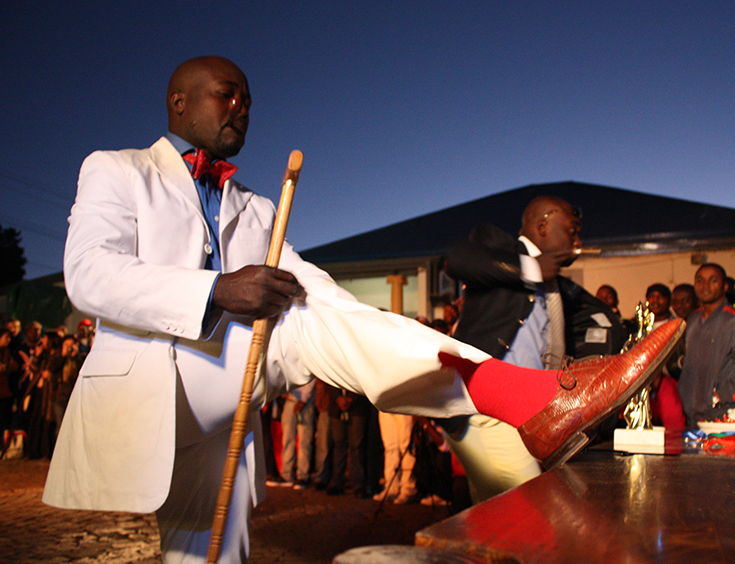 A Congolese national parades infront of fans during the La Sape competition at Kin Malebo restaurant, in Yeoville, Johannesburg South Africa, 30 May 2009. Sapeur ('Société des Ambiancé et Personnes Elégants') is a movement which dictates its members to wear European haut couture and was started by musician Papa Wemba. It sprang up after Mobutu Seseko's decree that everyone in Congo was expected to dress in African outfits.