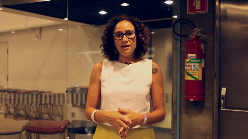 Maria Carolina Trevisan de pé e dando entrevista para o Geledés
