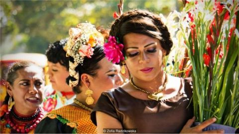 Travestis em uma passeata carregando flores
