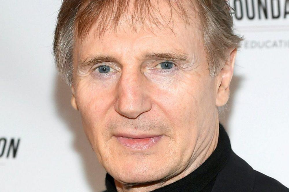 Rosto de Liam Neeson, homem branco de olhos azuis cabelos grisalhos e sinais de expressão no rosto.