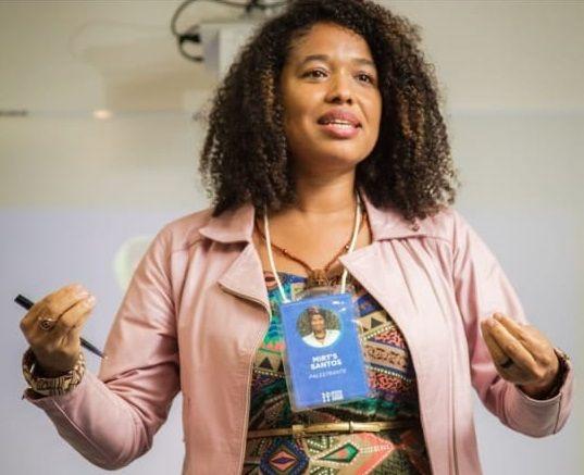 Mirts Sants, mulher negra de proximadamente 33 anos, com casaco salmão,cabelos soltos e gesticulando com as mãos
