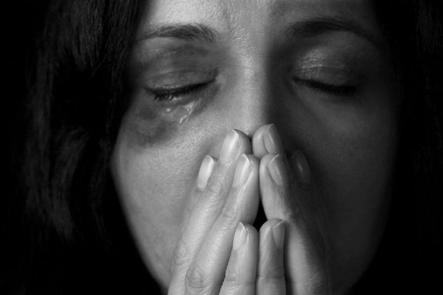 Mulher ferida e com a mão na boca feminicídio e violência