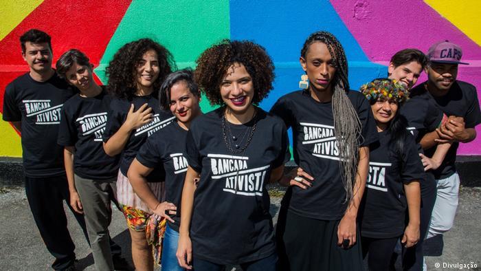 grupo de jovens vestido com camisas preta escrito bancada ativistas