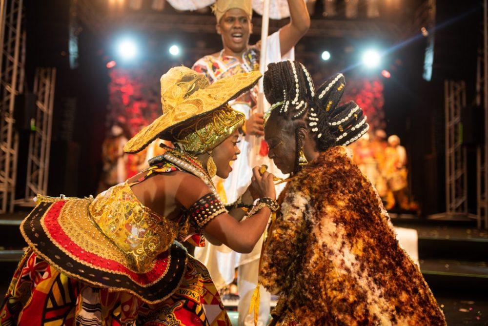 Mulher negra posando de realeza no palco