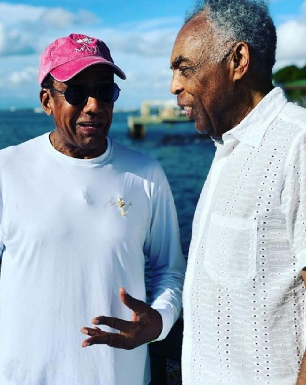 Jorge Ben Jor e Gilberto Gi converesando em pé, ambos com camiseta branca. Jorge Ben Jor usa oculos e um boné vermelho